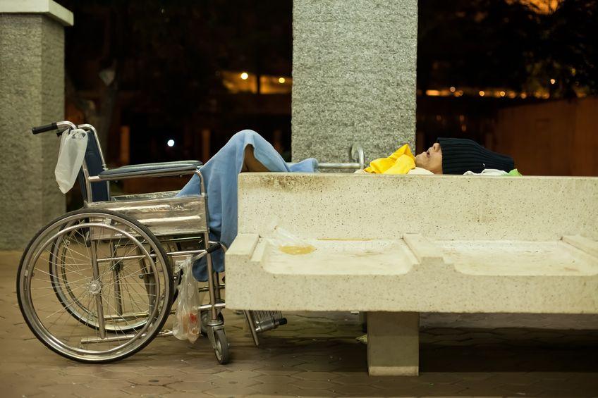 Homeless disabled man sleeping on a public concrete bench under bridge in downtown Bangkok, 2012