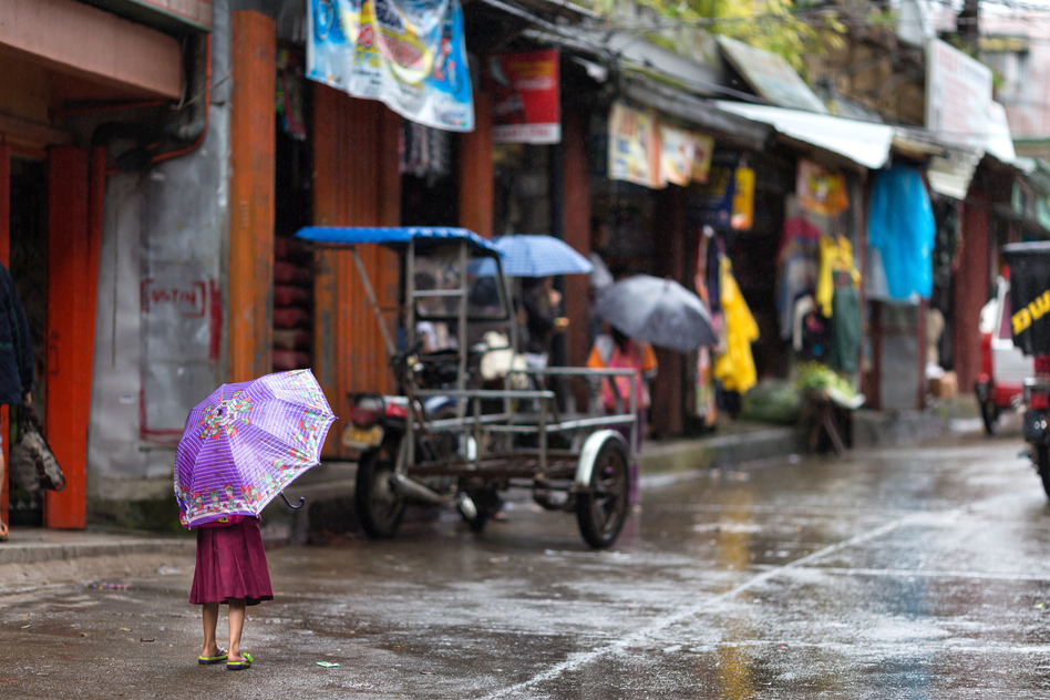 Cute little girl sheltering under a purple umbrella standing alone in the street in the rain in Banuae village, Philippines looking towards people sheltering in colorful shops